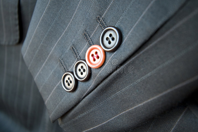 Business difference / Red suit button standing out. Close-up shot of a businessman striped suit with a red button standing out among other buttons stock photography