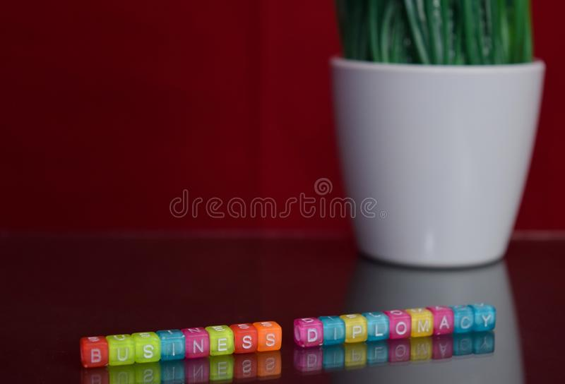 Business diplomacy text at colorful wooden block on red background. Desk office and education concept stock photos