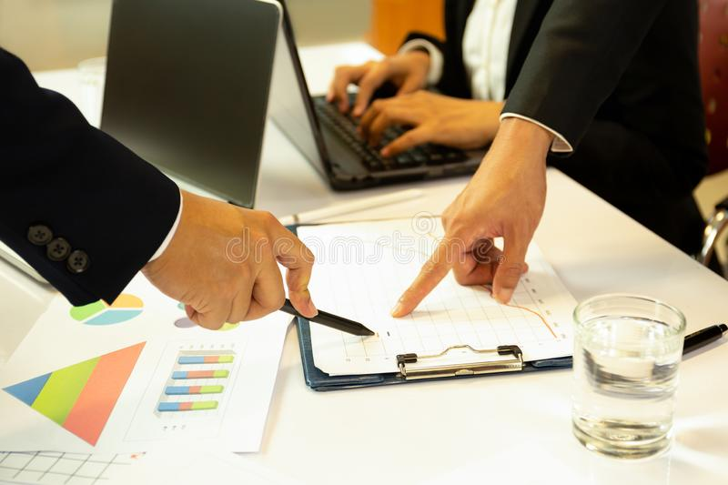 Business discussing financial matter hands with pen pointing at financial graph. stock images