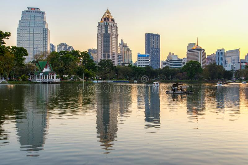 Business district cityscape from a park with sunset time from Lumpini Park, Bangkok royalty free stock photography