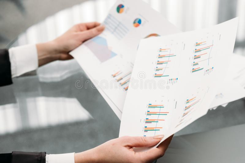 Business document graph data statistics report. Business documents graphs. hands holding papers. report statistics data analysis. office workplace royalty free stock photography