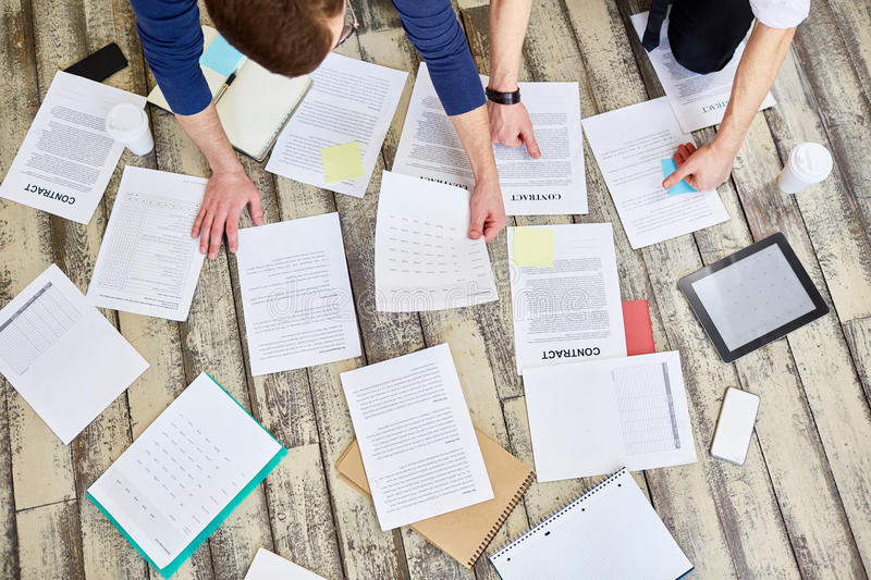 Business Documentation Laid Out on Office Floor. Above view of assorted documents and contracts laid out on wooden office floor with hands of two unrecognizable stock image