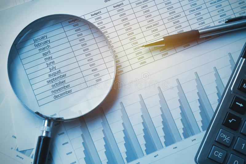 business documents accounting with calculator, pen and magnifying glass. concept for financial stock photography