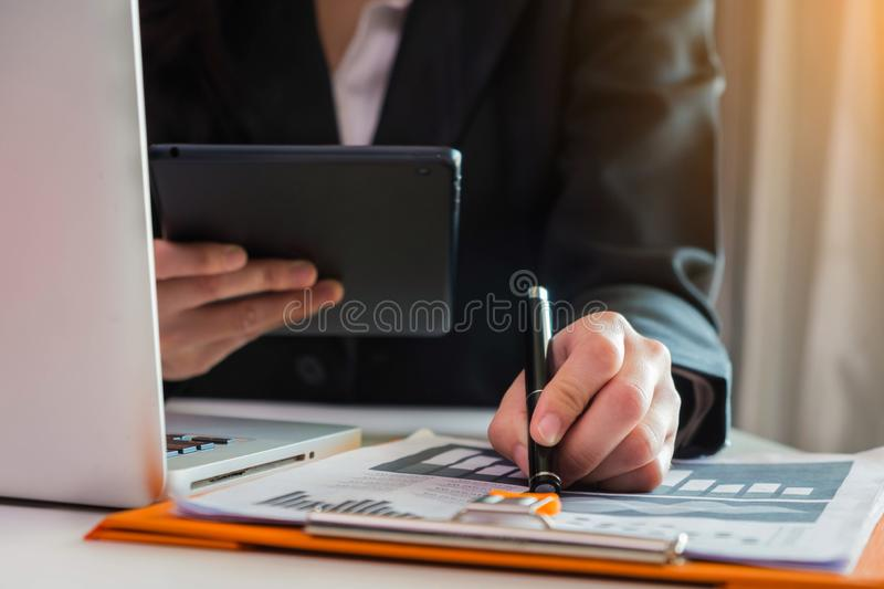 Business documents on office desk with laptop and smart phone. stock photo