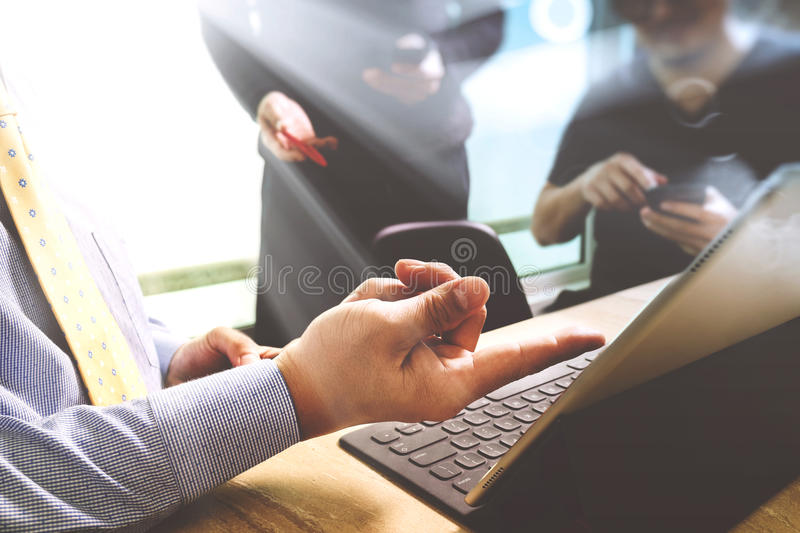 Business documents on office table with smart phone and laptop c. Omputer and graph financial with social network diagram and three colleagues discussing data in stock image
