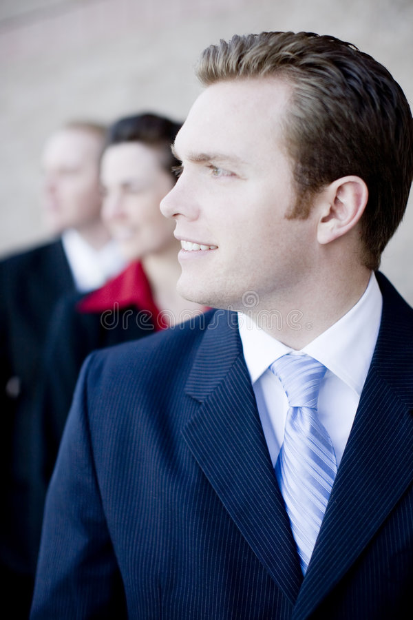 Business dream team. Attractive businesspeople wearing formal clothing standing in a line looking in same direction and smiling royalty free stock images