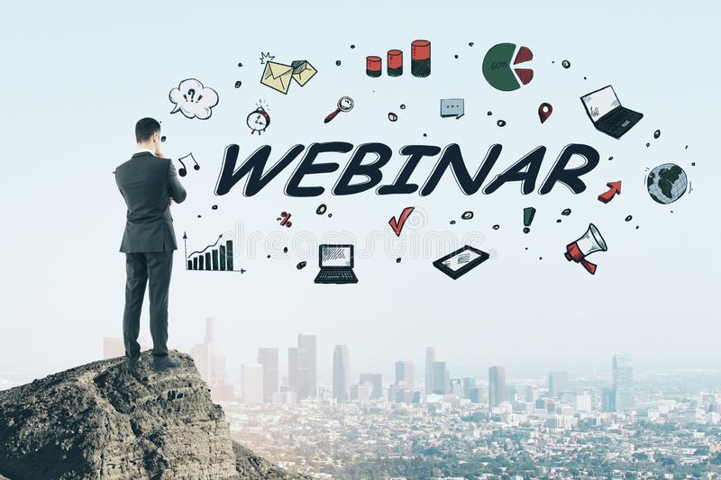 Business e-learning training concept with businessman on rock top and hand drawn webinar word.Double exposure stock images