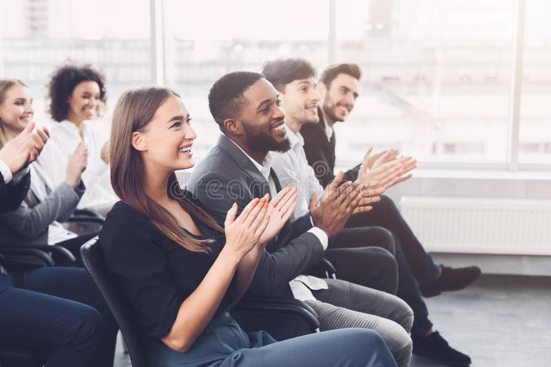 Business education. Colleagues clapping hands at seminar. Listening speaker royalty free stock image