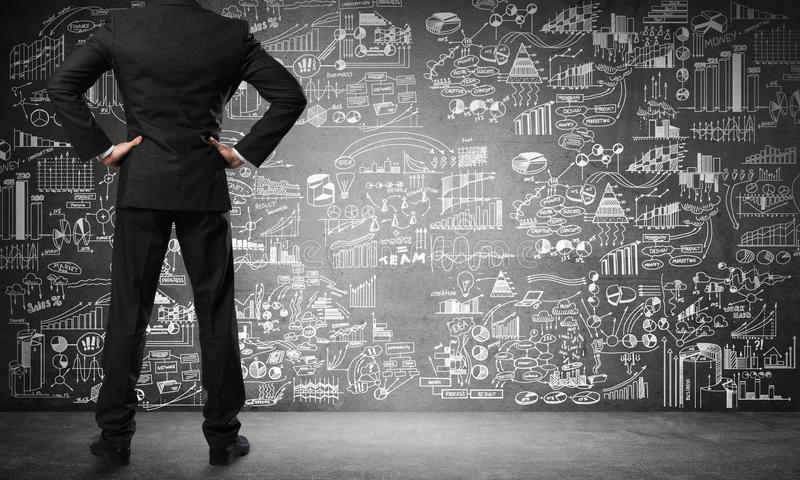 Business education concept. Back of businessman looking at business sketches on chalkboard stock photo