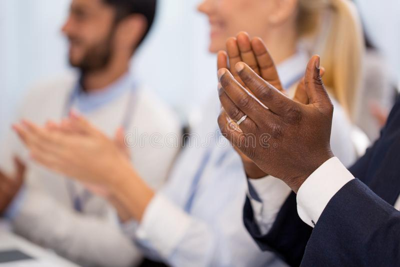 Happy people applauding at business conference stock images