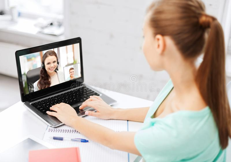 Woman or student having video call on laptop. Business, education and technology concept - women or student having video call with customer service operator or stock image