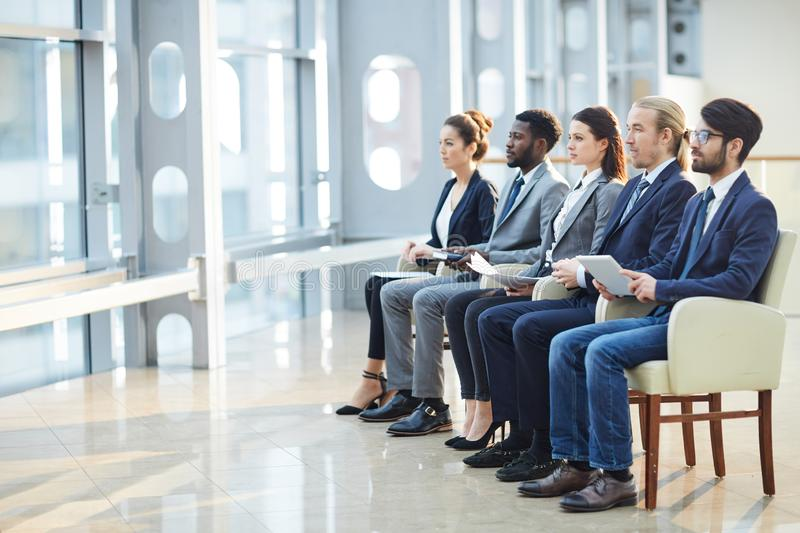 Business employees watching presentation. Group of concentrated young business employees in formalwear sitting in row and watching presentation together at royalty free stock images