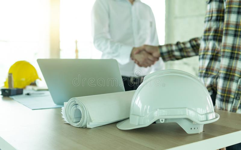 Business engineer contractor concept,white helmet with office tool on table and handshake of architecture and businessman investor royalty free stock images