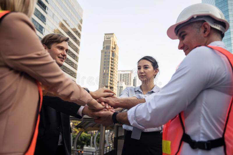 Business and engineer team join hands in city stock image