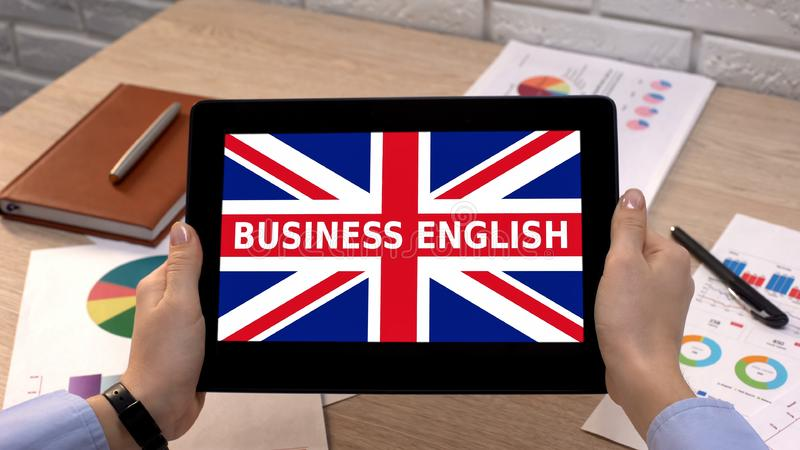 Business English app against Britain flag on tablet in female hands, tutorial royalty free stock image