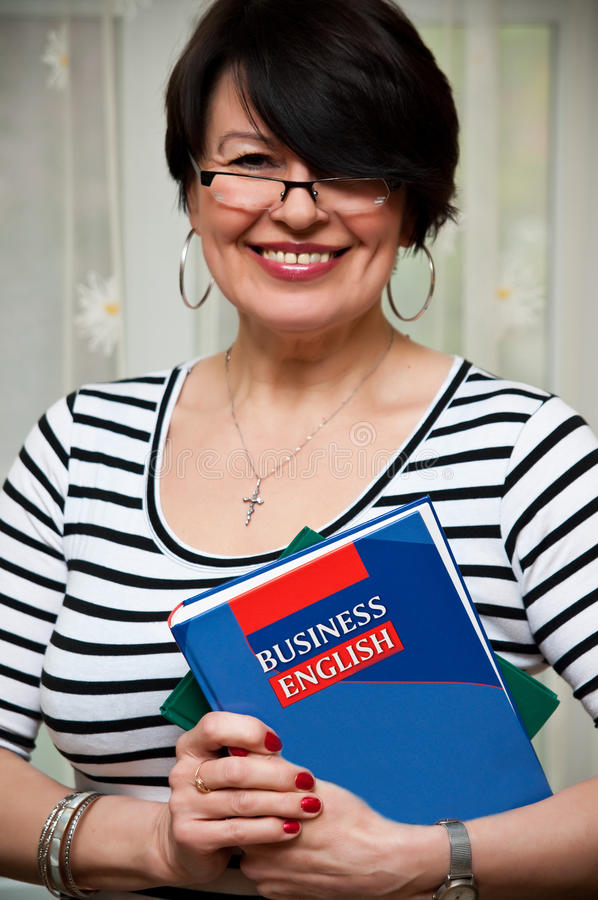 Business English teacher. Smiling middle aged female teacher with business English book stock photos