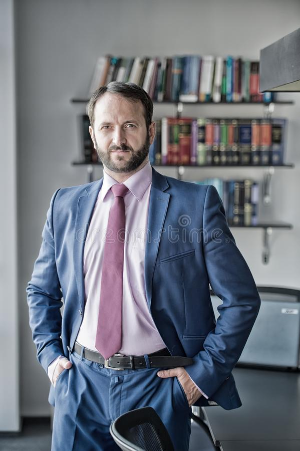 Business, entrepreneurship concept. Businessman or director pose at workplace. Man with beard in blue formal suit. Fashion, style, dress code. Career royalty free stock photography