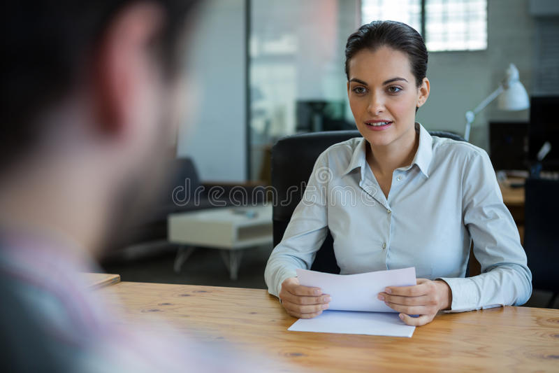 Business executive conducting job interview with man. In office royalty free stock image