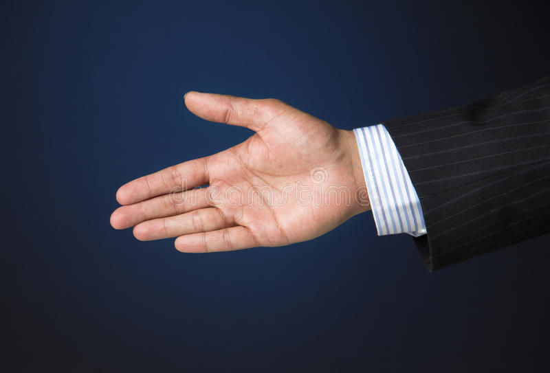 Business executive extending arm to shake hands stock photo