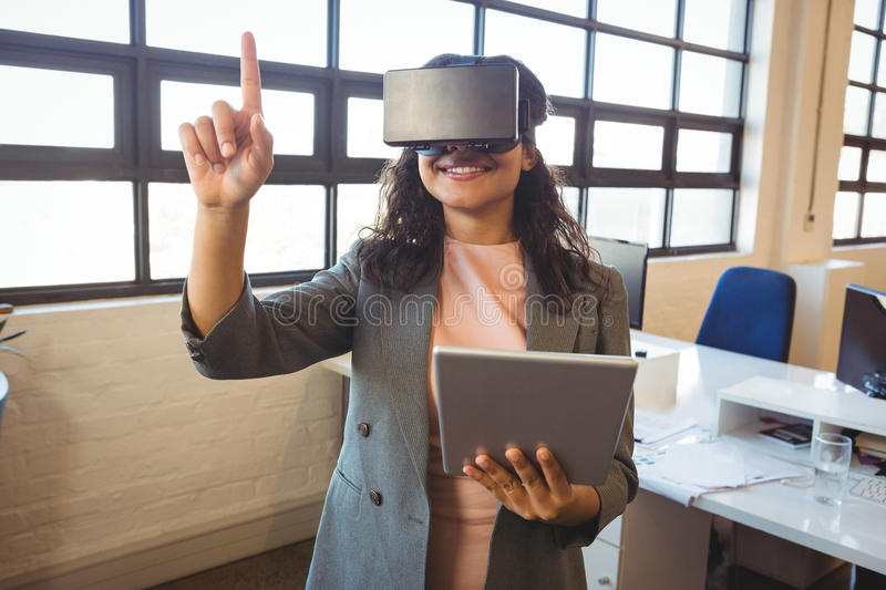 Business executive holding digital tablet while using virtual reality headset royalty free stock images