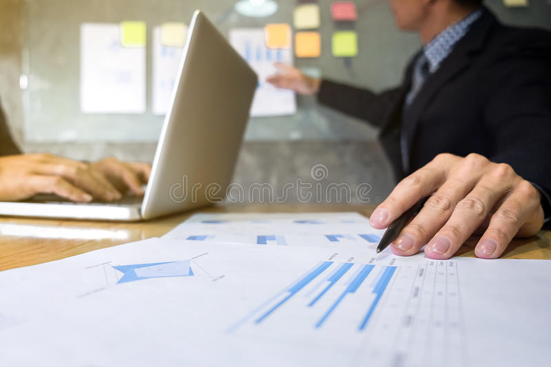Business executive pointing graph presentation to colleagues in. Office, during meeting, explaining, consultation stock photography