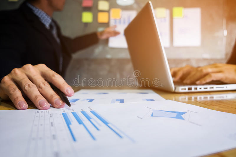 Business executive pointing graph presentation to colleagues in. Office, during meeting, explaining, consultation royalty free stock images
