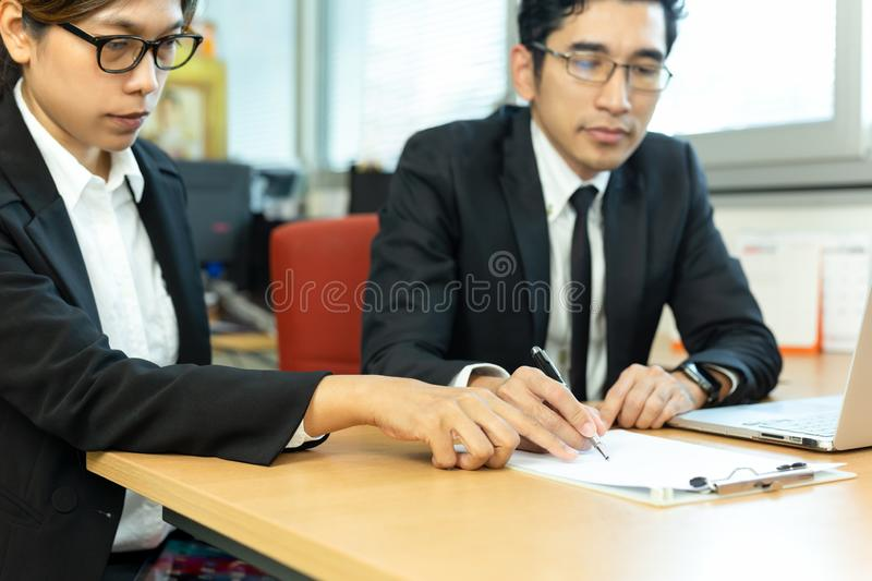 Business executive signing contracts with secretary at desk in office. stock photo