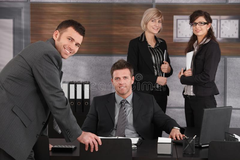 Business executive with team around. Business executive sitting in office, looking at camera with team standing around royalty free stock images