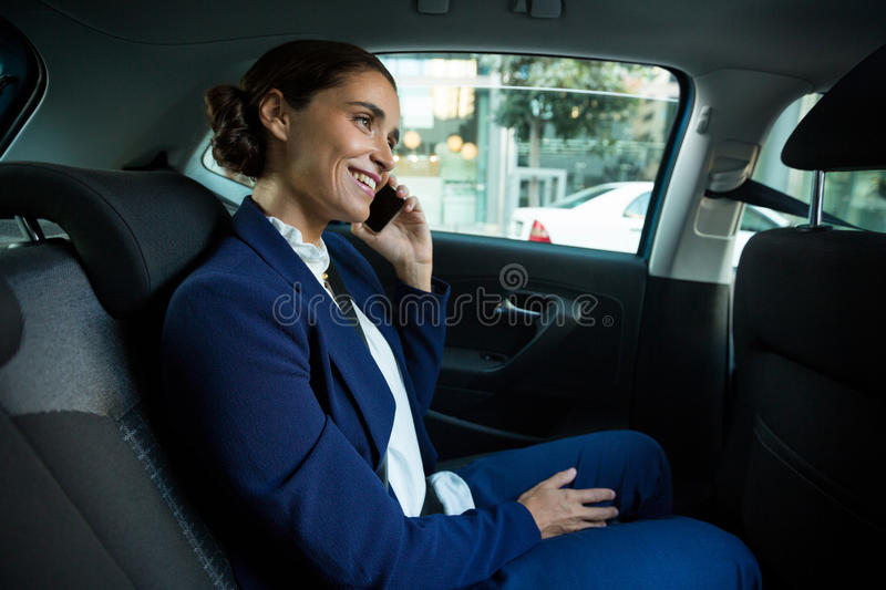 Business executive talking on mobile phone in car royalty free stock photo