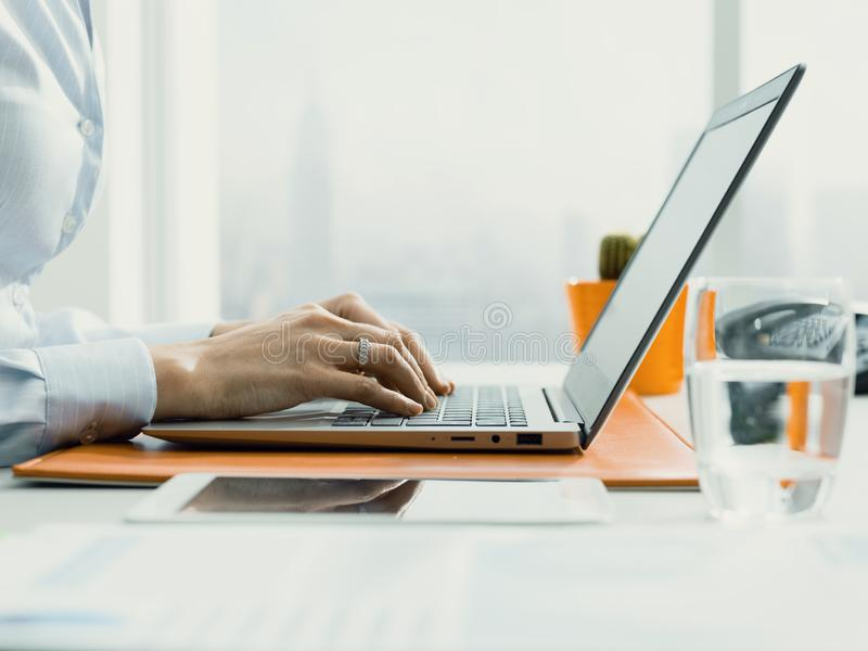 Business executive working with a laptop and connecting online. Female business executive sitting at desk and working with a laptop, business and communication stock photo