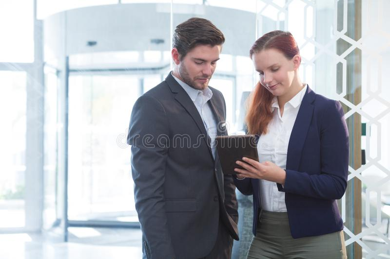 Business executives discussing over digital tablet stock images