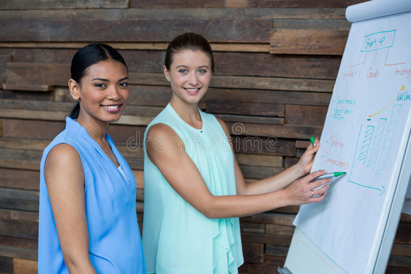 Business executives discussing over white board in office stock photos