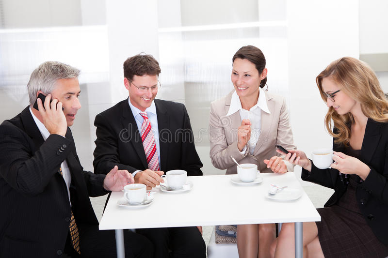Business executives enjoying coffee. Business executives sitting around a table enjoying a relaxing cup of coffee together during a break royalty free stock image