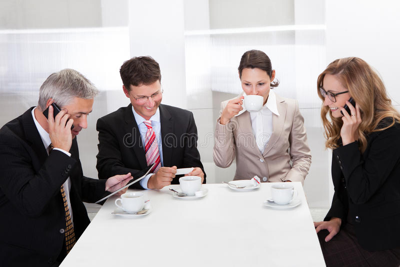 Business executives enjoying coffee. Business executives sitting around a table enjoying a relaxing cup of coffee stock photos