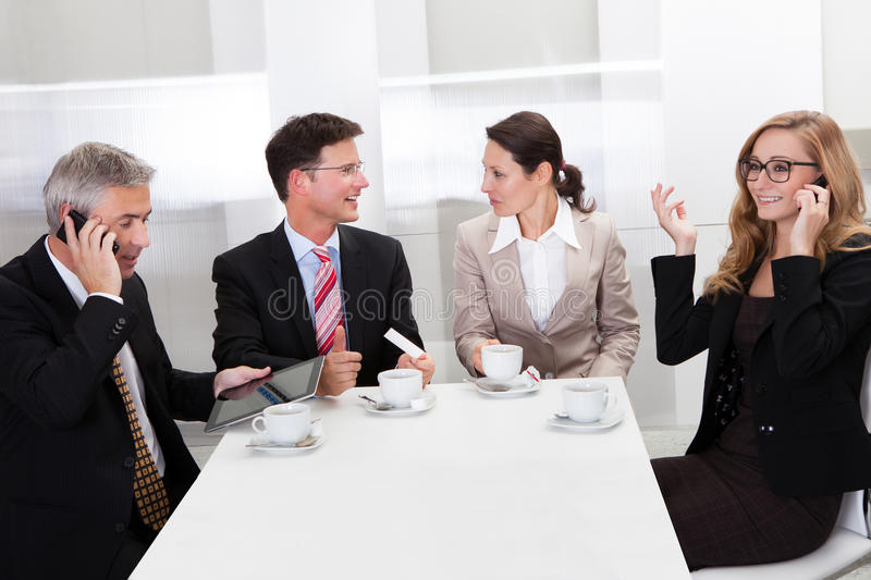 Business executives enjoying coffee. Business executives sitting around a table enjoying a relaxing cup of coffee together during a break stock images