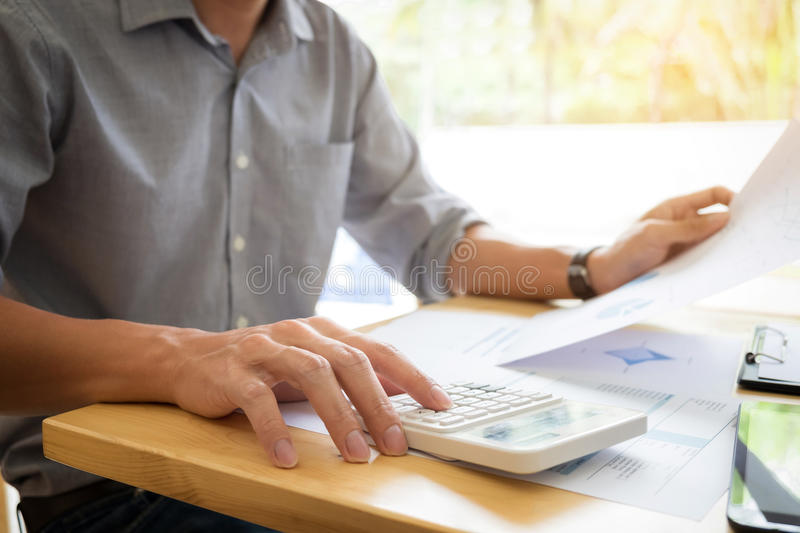 Business executives hands using calculator to calculate tax Invoice and set new project business strategy plan with data document royalty free stock photography