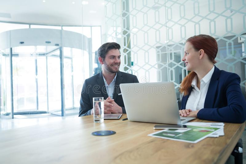 Business executives interacting while using laptop stock image