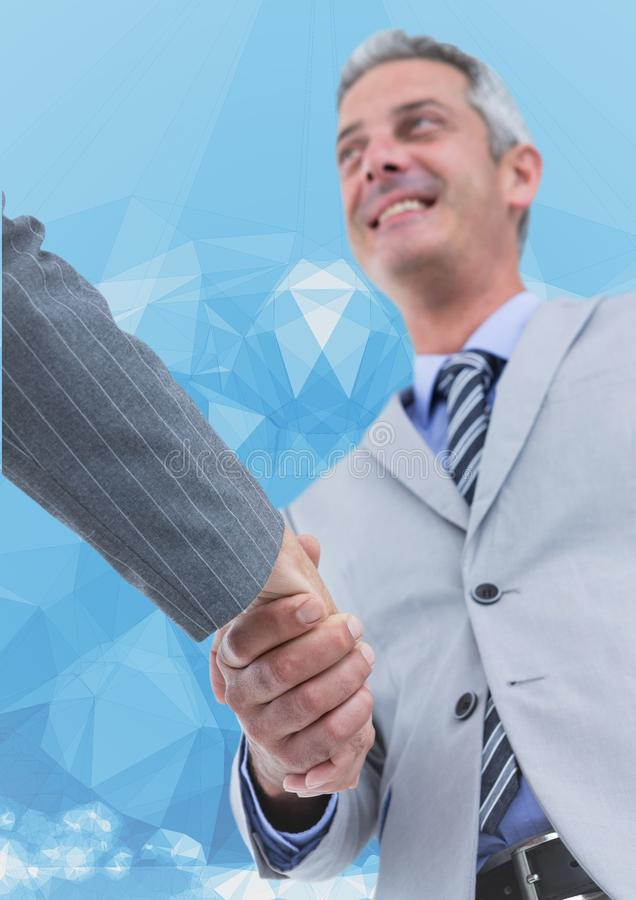 Business executives shaking hands against blue background royalty free stock photos