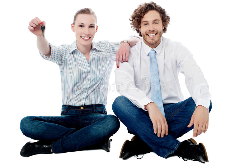 Business executives sitting on the floor. Woman sitting with her boss and showing the key stock photos