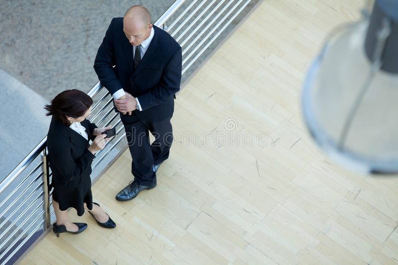 Business executives standing together while businesswoman using mobile phone stock photography