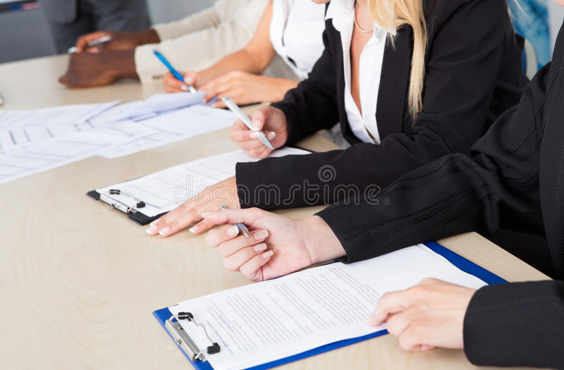 Business executives taking notes during a meeting. Group of business executives taking notes during a meeting at office royalty free stock images