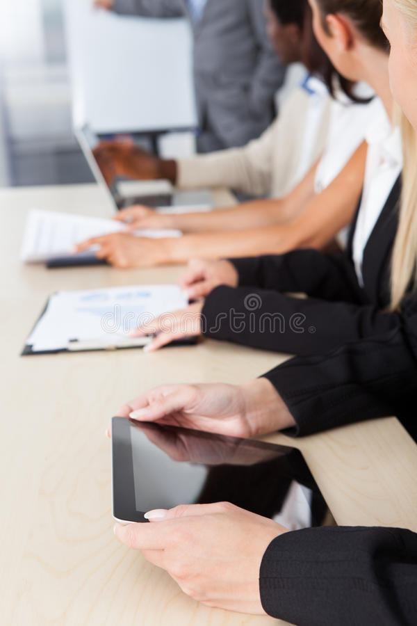 Business executives taking notes during a meeting. Group of business executives taking notes during a meeting at office royalty free stock photography