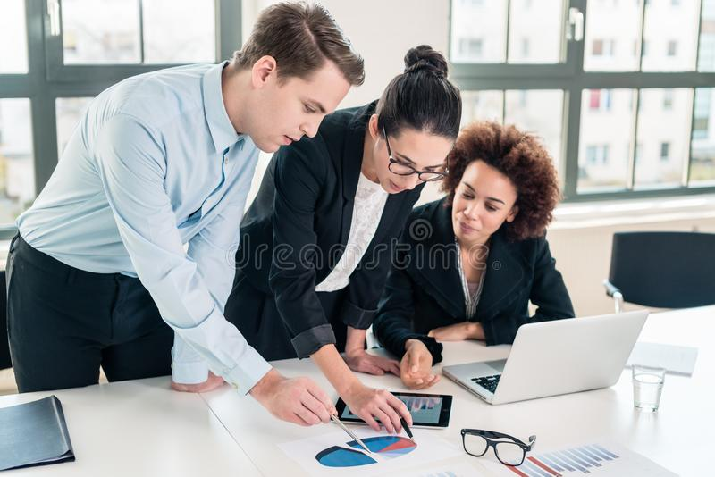 Business experts interpreting pie chart printed on paper. Young team of three business experts interpreting pie chart printed on paper in the office stock photo