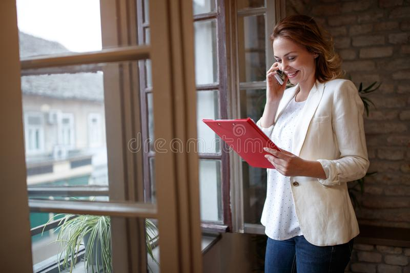Business female in company talking on cell phone with client stock photography