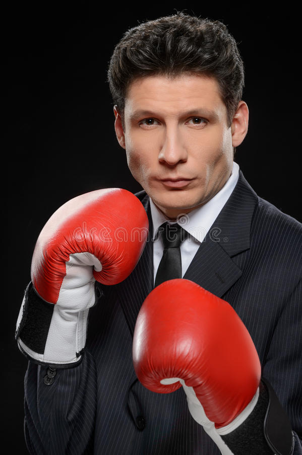 Business fighter. Portrait of confident businessman in red boxing gloves standing against black background royalty free stock photography