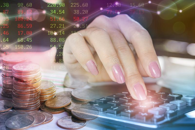 Business and finance concept ,coins, woman hand calculating ,business stock chart background. Double exposure business and finance concept ,coins, woman hand stock photo