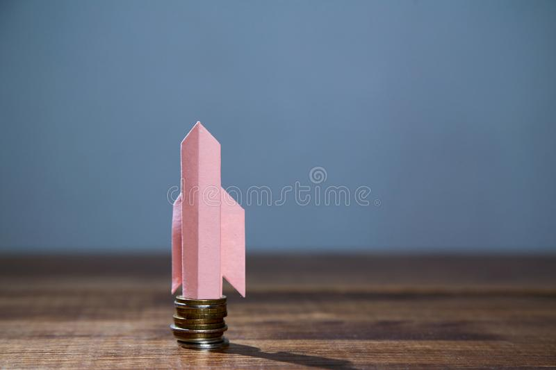 Business, finance, investment, saving and stock market concept. Paper rocket taking off from a stack of coins stock image