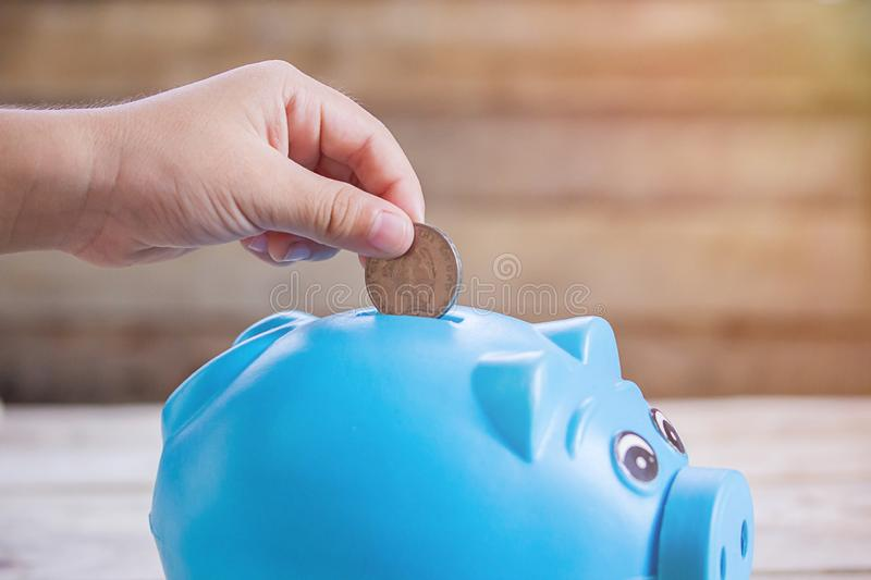 Business or finance saving concept with hand putting coin into b stock photography