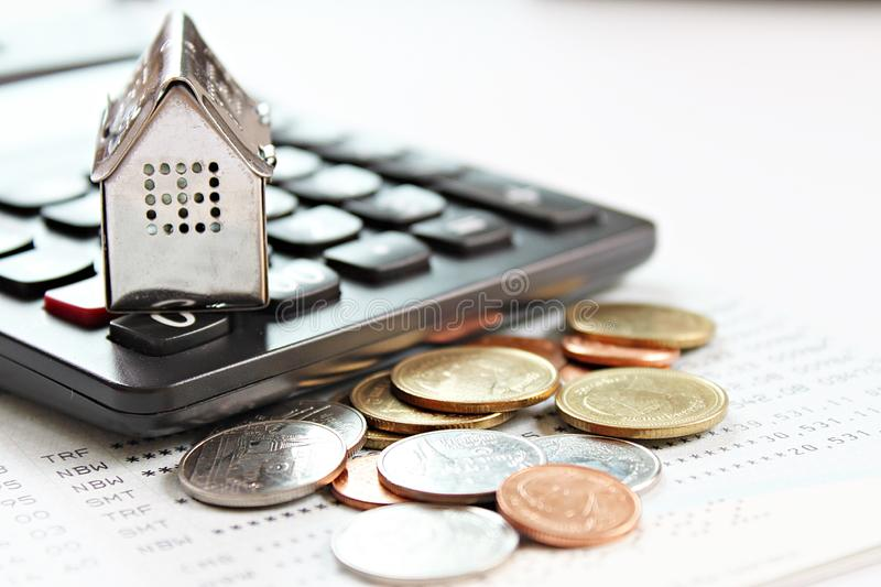 House model, calculator and coins on savings account passbook or financial statements. Business, finance, saving money, property ladder or mortgage loan concept stock photo