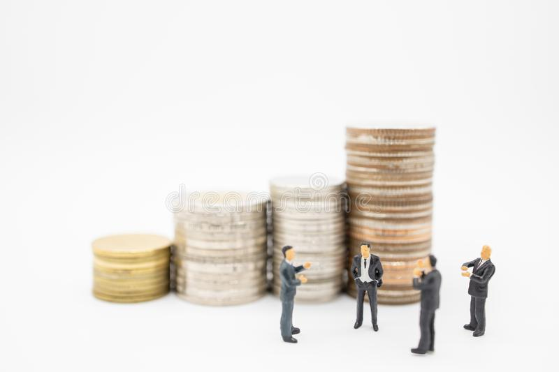 Business, Finance, Saving and teamwork concept. Close up of group of businessman minature figures standing and clap applaud. Appreciation with stack of coins stock images
